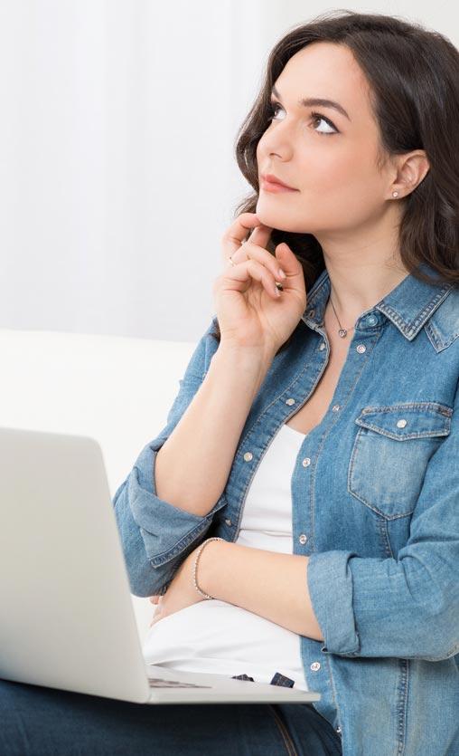 Braunhaarige Frau, die vor ihrem Laptop auf dem Sofa sitzt und nachdenklich zur Seite blickt.