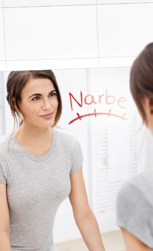 Braunhaarige Frau mit tiefem Zopf, die sich in einem Spiegel anschaut und lächelt. Auf den Spiegel ist in rot