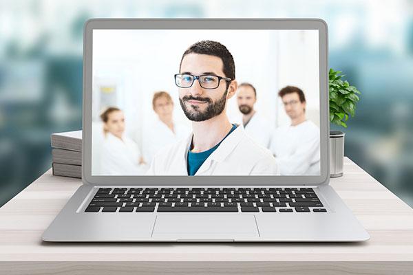 Ein Laptop steht auf einem Tisch. Der Bildschirm zeigt ein Team von Ärzten, wobei ein dunkelhaariger Mann mit Brille im Vordergrund steht und in die Kamera lächelt.