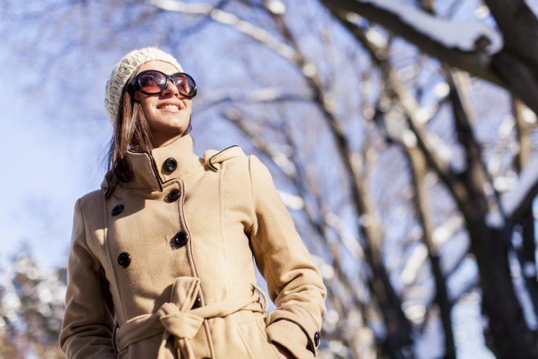 Eine Frau mit Mütze, Mantel und Sonnenbrille lacht an einem schönen Wintertag der Sonne entgegen.