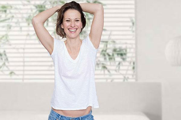 Lachende Brünette in Jeans und weißem T-Shirt. Ihr Bauch ist etwas zu sehen.