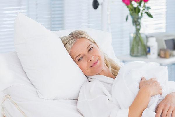 Eine blonde Frau liegt in einem weißen Krankenhausbett und lächelt in die Kamera.