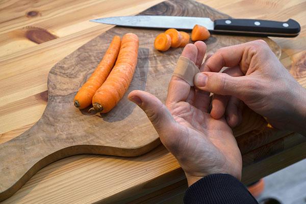 Eine Person wickelt sich ein Pflaster um den Finger, an dem sie sich beim Karottenschälen geschnitten hat.
