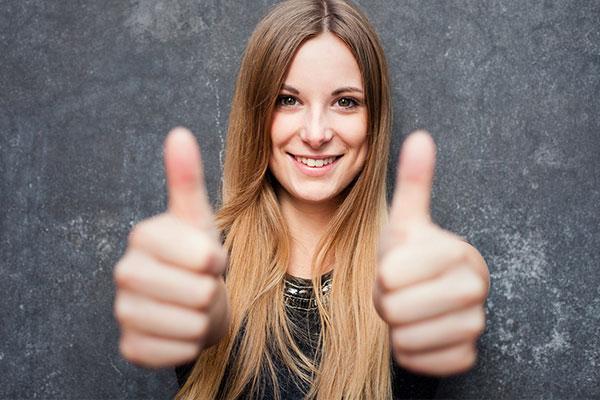 Eine junge Frau mit langen hellbraunen Haaren lacht in die Kamera und hält ihre beiden Daumen hoch.