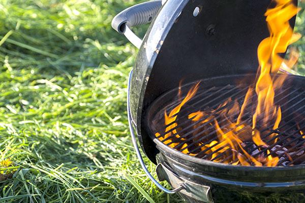 Ein Kugelgrill mit brennenden Kohlen steht auf einer Wiese.