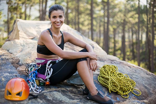 Eine Frau mit Kletterausrüstung sitzt auf einem Felsen und lacht in die Kamera.